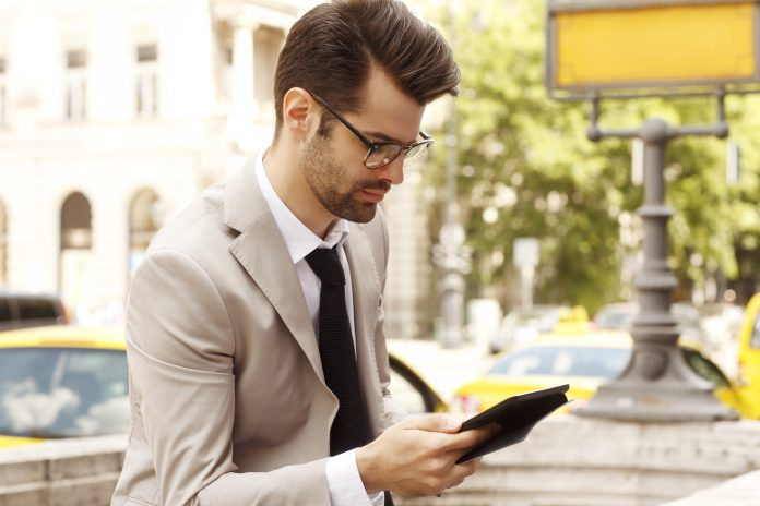 Modern businessman holding a verizon tablet