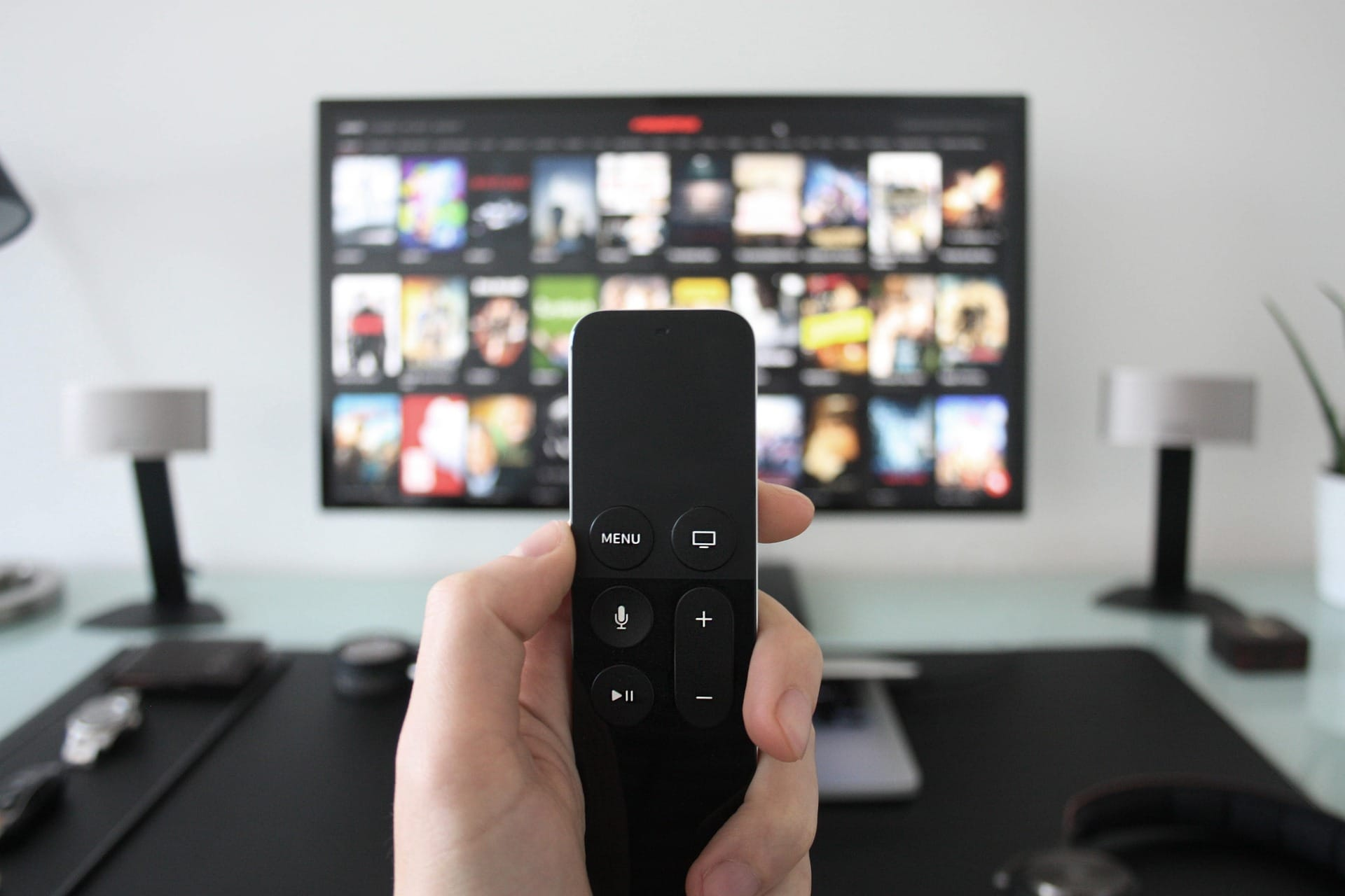 Man holding a Remote that will operate the movie he will stream on the TV