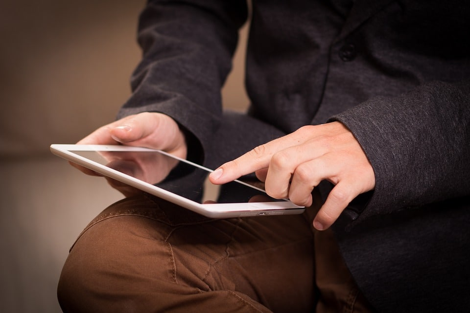 Man Tapping the Screen of the Tablet