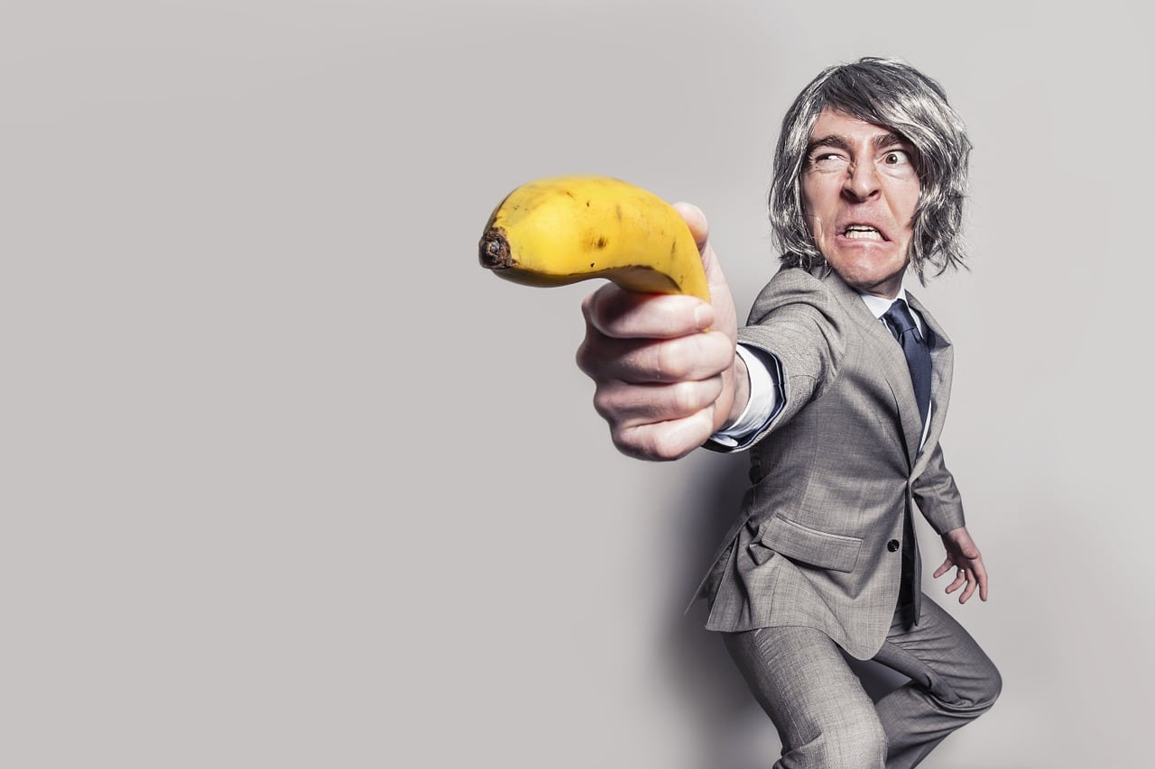 Wht is artificial intelligence? Comedian with a banana pointing it like a gun